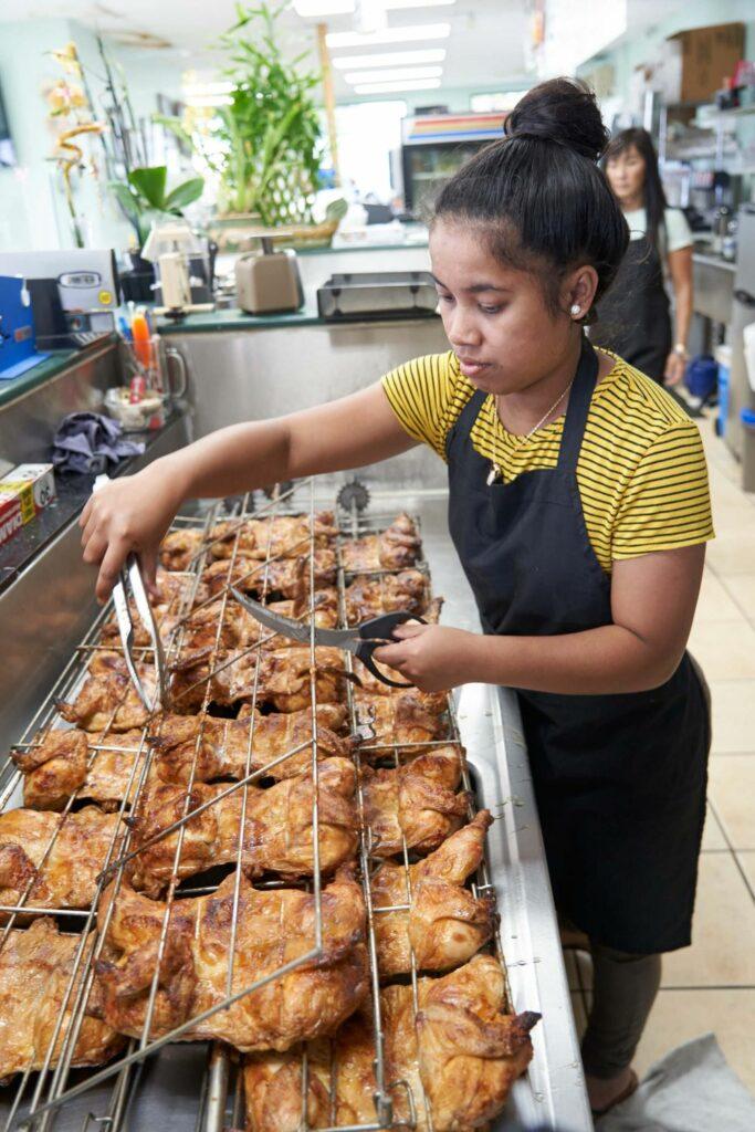 チキンを店内で網から外す女性
