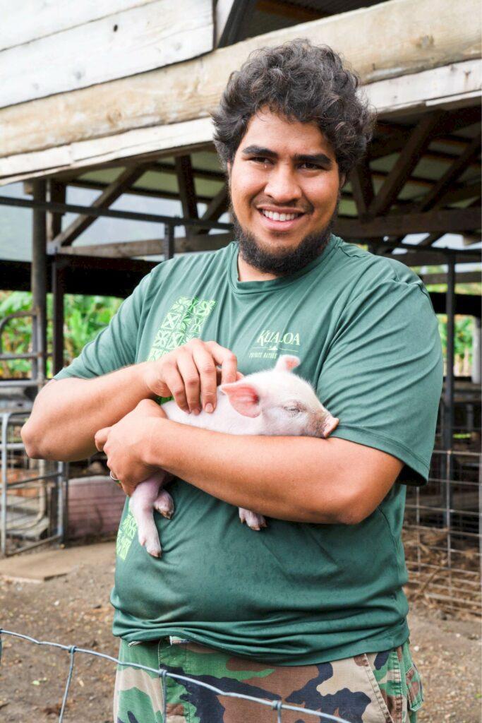 子豚を抱くスタッフ